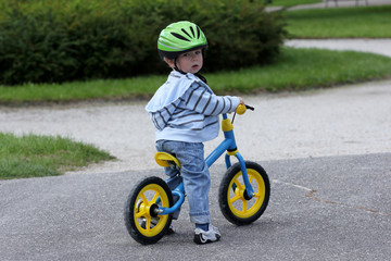 Child learning to ride on his first bike
