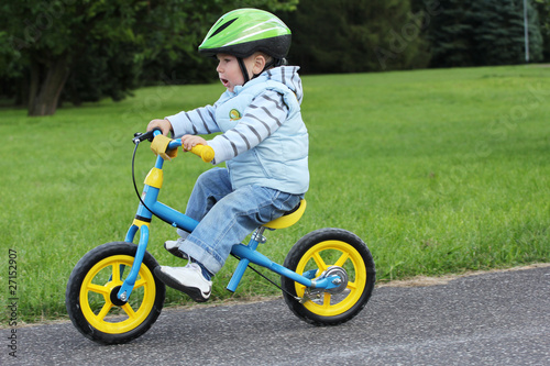 Child learning to ride on his first bike - 27152907