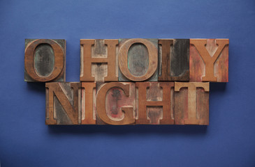 the words O holy night in old ink-stained letterpress wood type