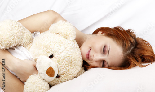 Woman in white nightie lying in the bed with soft toy.