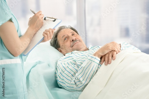 Nurse taking notes of old patient