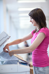 pretty young woman using a copy machine (shallow DOF; color tone