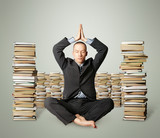 businessman in lotus pose with many books near