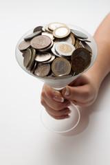 бокал в монетами в руке