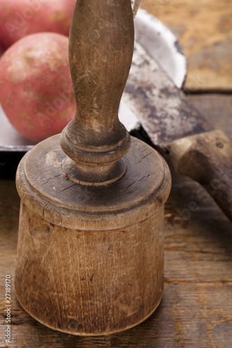 antique potato masher on  old wooden table with knife and potato