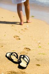 Beach slippers on sand and female feet