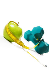 Healthy Lifestyle -Green apple, tape measure and weights