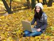 Beautiful woman working on laptop in park during autumn season
