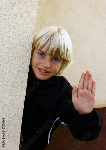 enfant blond saluant de la main