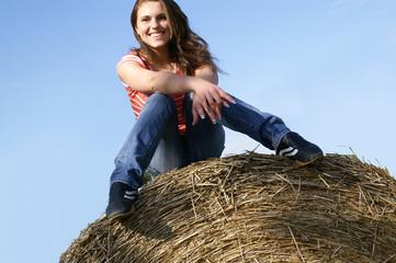 Lachendes Mädchen auf der Strohrolle