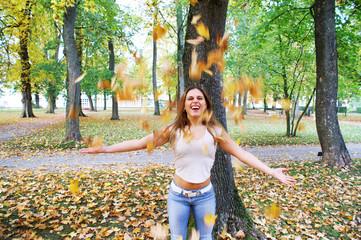Mädchen spielt mit den Herbstblättern