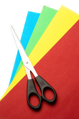 Colored paper and scissors isolated on white