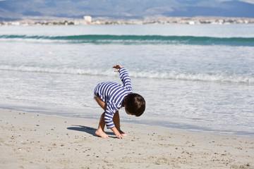bambino raccoglie sabbia