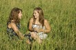Two Young Women Talking In Field