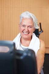 Lachende Seniorin im Fitnesscenter