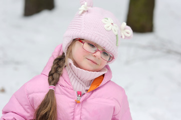 winter  girl in glasses and pink hat and jacket in the forest