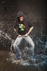 Hip-hop dancer in aqua studio showin his tongue
