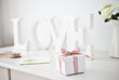 """wooden """"love"""" letters decoration and gift box with ribbon on desk"""