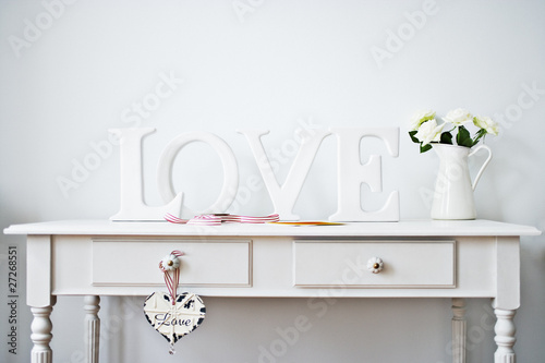 """love"" decorations, ribbon, roses and card on desk"