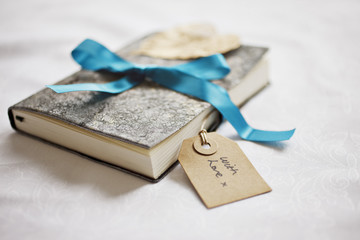 close up of book tied with ribbon and gift tag