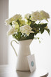 card leaning against white rose bouquet in pitcher