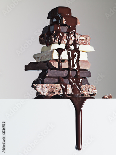 chocolate syrup dripping over stack of chocolate bars
