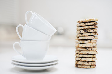 stack of coffee cups next to stack of cookies