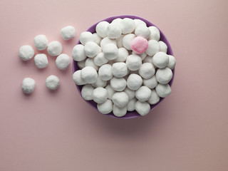 bowl of white bon bons and one pink mint