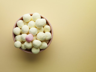 bowl of yellow bon bons and one pink mint