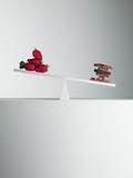chocolate bars tipping seesaw with strawberries on opposite end