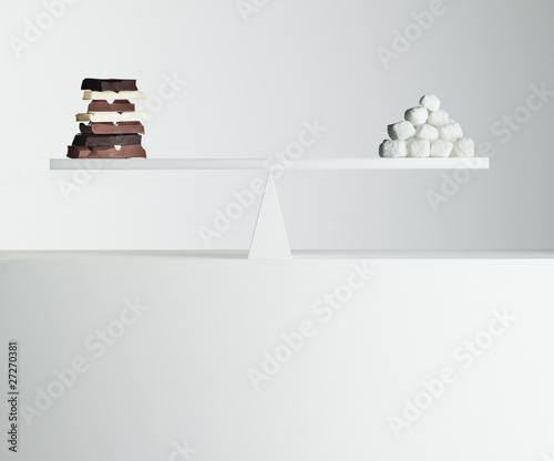 chocolate bars and stack of sugar cubes balanced on seesaw