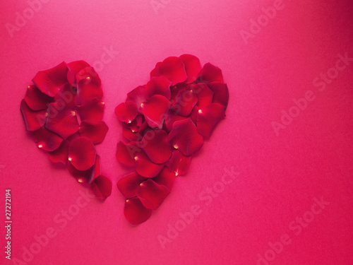 red rose petals forming broken heart-shape