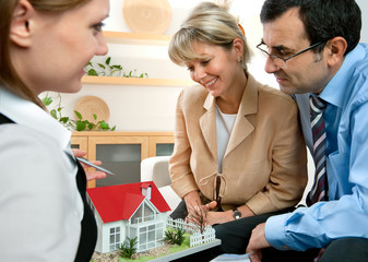 Couple discussing  with real estate agent or architect