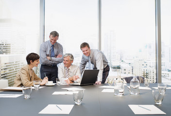 business people working at laptop in conference room overlooking city