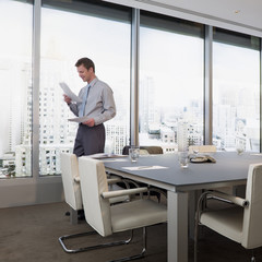 man reviewing paperwork at conference room window overlooking city
