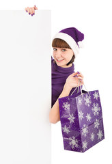 Woman with shopping bag in Santa hat holding blank billboard