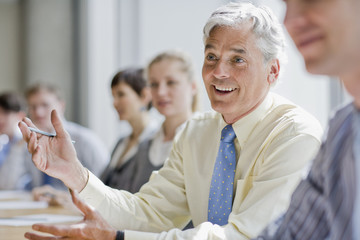 smiling businessman gesturing in meeting