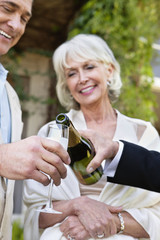 well-dressed senior couples pouring champagne