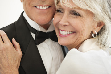 close up of well-dressed senior couple smiling and hugging