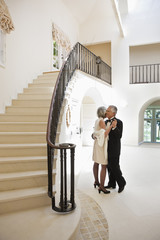 well-dressed senior couple dancing in foyer