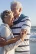 smiling senior couple hugging on beach