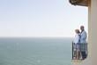 senior couple in bathrobes on balcony overlooking ocean