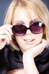 Blonde Frau blickt durch Brille, hoch