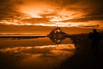 Mont Saint Michel reflected in the bay at sunset, France