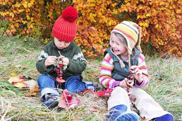 Geschwister basteln im Herbst