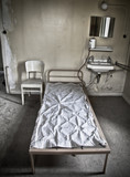 Fototapety A bed sitting in a room of an abandoned hospital