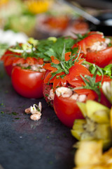 A cold buffet with the stuffed tomatoes in focus