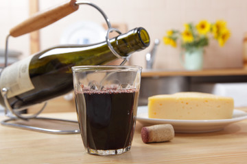 Glass of red wine and the slice of cheese on a rustic table