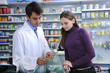 Pharmacist advising client at pharmacy