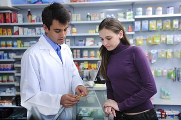 Pharmacist advising client at pharmacy